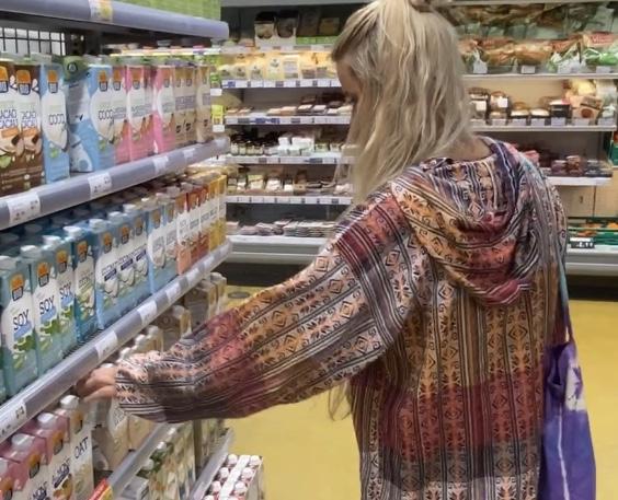 Frau im Supermarkt vor dem Milchregal.