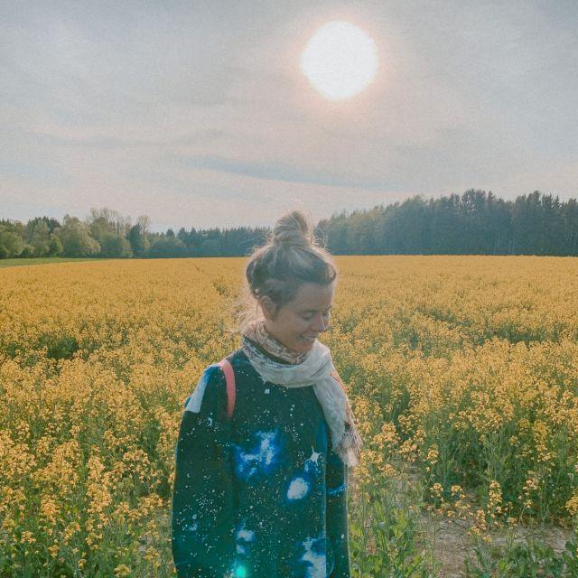 Frau steht vor einem gelben Rapsfeld, im Hintergrund die Sonne.