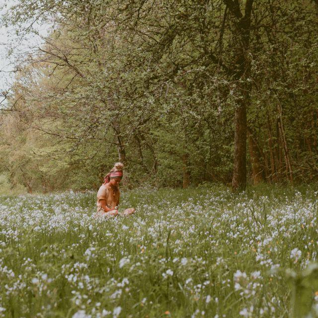 Frau sitzt in einer Blumenwiese.