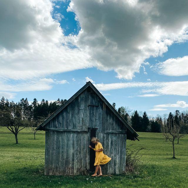 Frau im gelben Kleid vor Holzhütte und großen Wolken im Hintergrund.