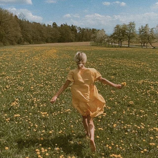 Frau rennt im gelben Kleid über gelbe Blumenwiese.