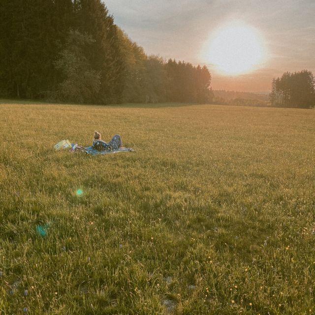 Frau auf einer großen Wiese beim Sonnenuntergang.