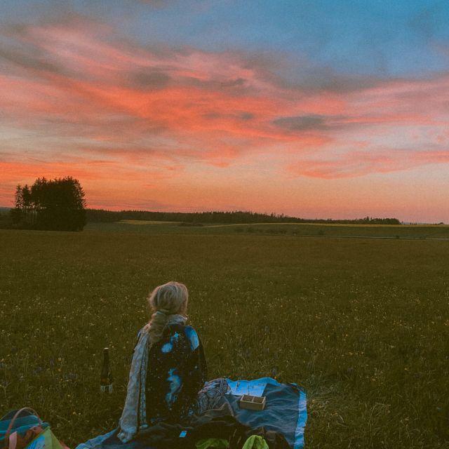Frau vor einem roten Sonnenuntergang.
