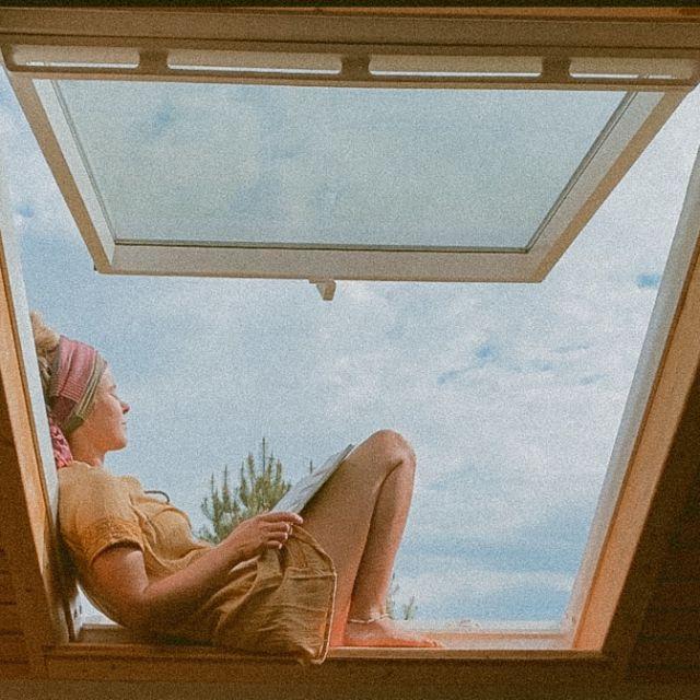 Frau sitzt im Fenster beim Lesen.