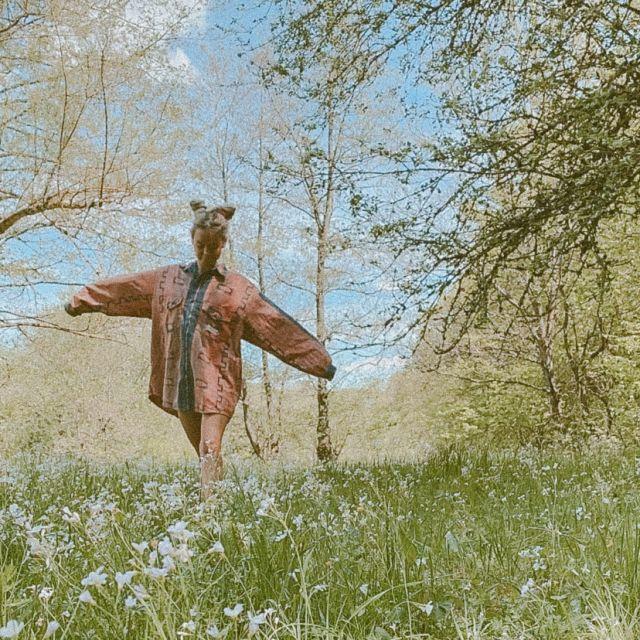 Frau läuft durch Blumenwiese.