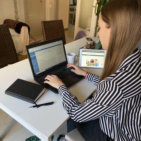 Ein Mödchen, das an einem Laptop arbeitet.