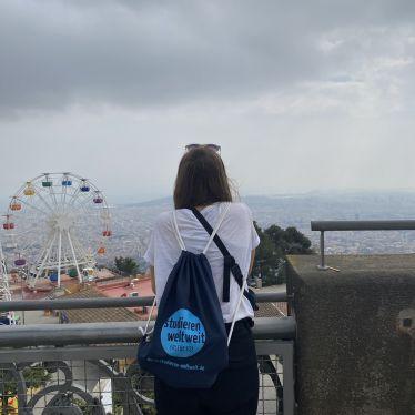 Ein Mädchen von hinten, das von einer Aussichtsplattform über Barcelona blickt