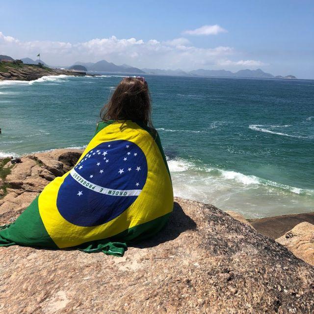 Mmädchen sitzt auf einem Stein an einer Klippe. Sie ist zugedeckt mit der brasilianischen Flagge.