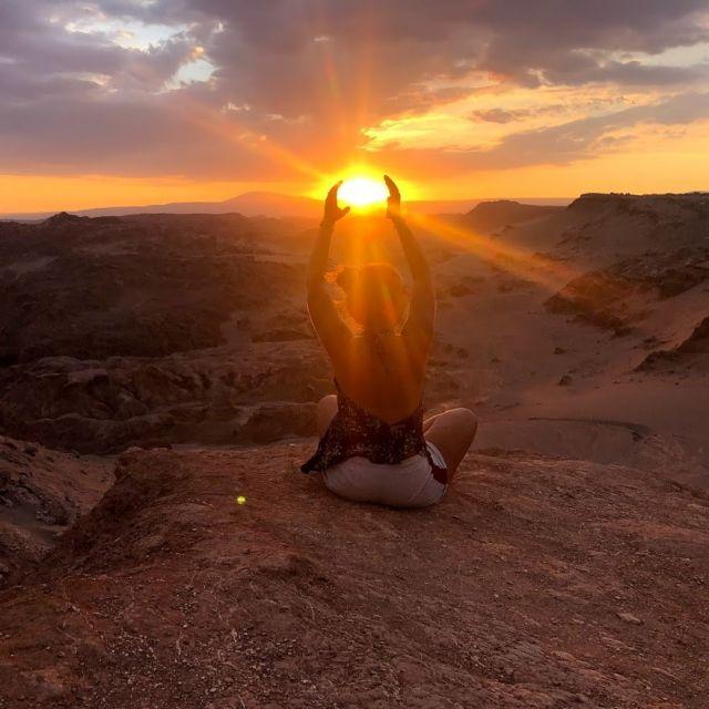 Mädchen sitzt an einer Klippe und hält ihre Hände hoch, sodass es aussieht, als würde sie die Sonne halten.