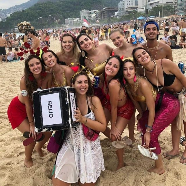 Eine Gruppe junger Leute stehen verkleidet am Strand.
