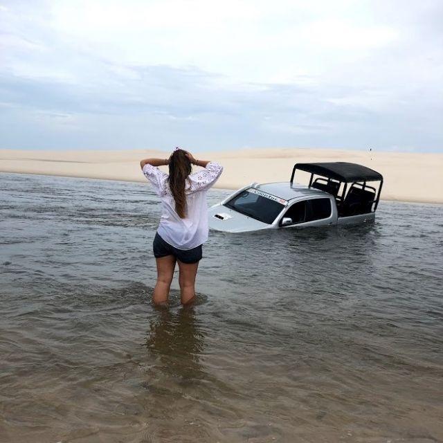 Mädchen steht in einem Teich und schlägt die Hände über den Kopf. Im Hintergrund liegt ein Truck versunken im Wasser.