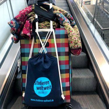 Ein Koffer steht auf der Rolltreppe mit einer Tasche auf der studieren weltweit steht.