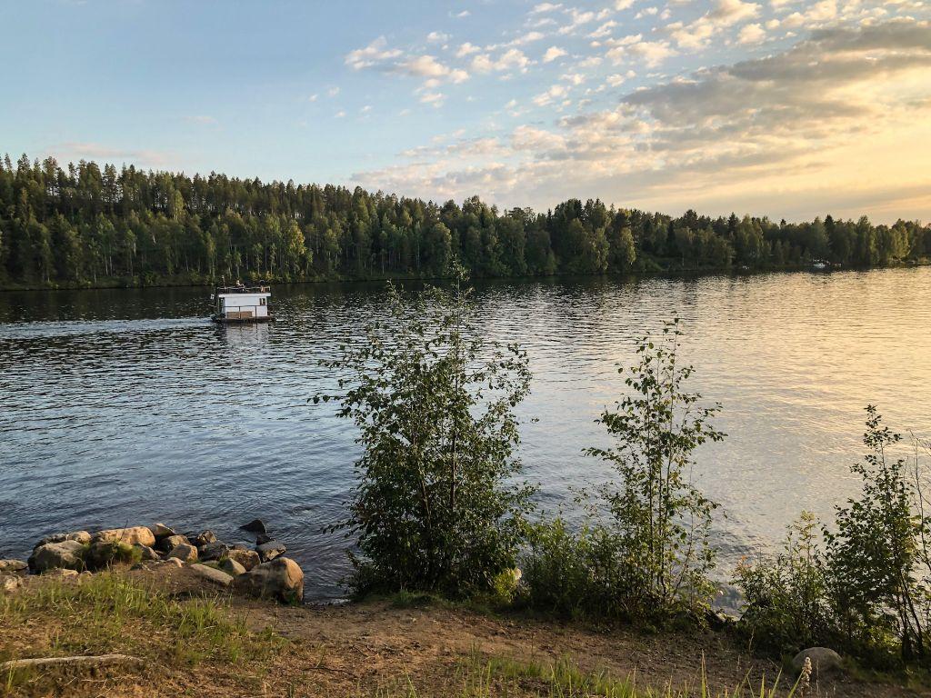 kleines eckiges Boot im Sonnenuntergang auf Fluss
