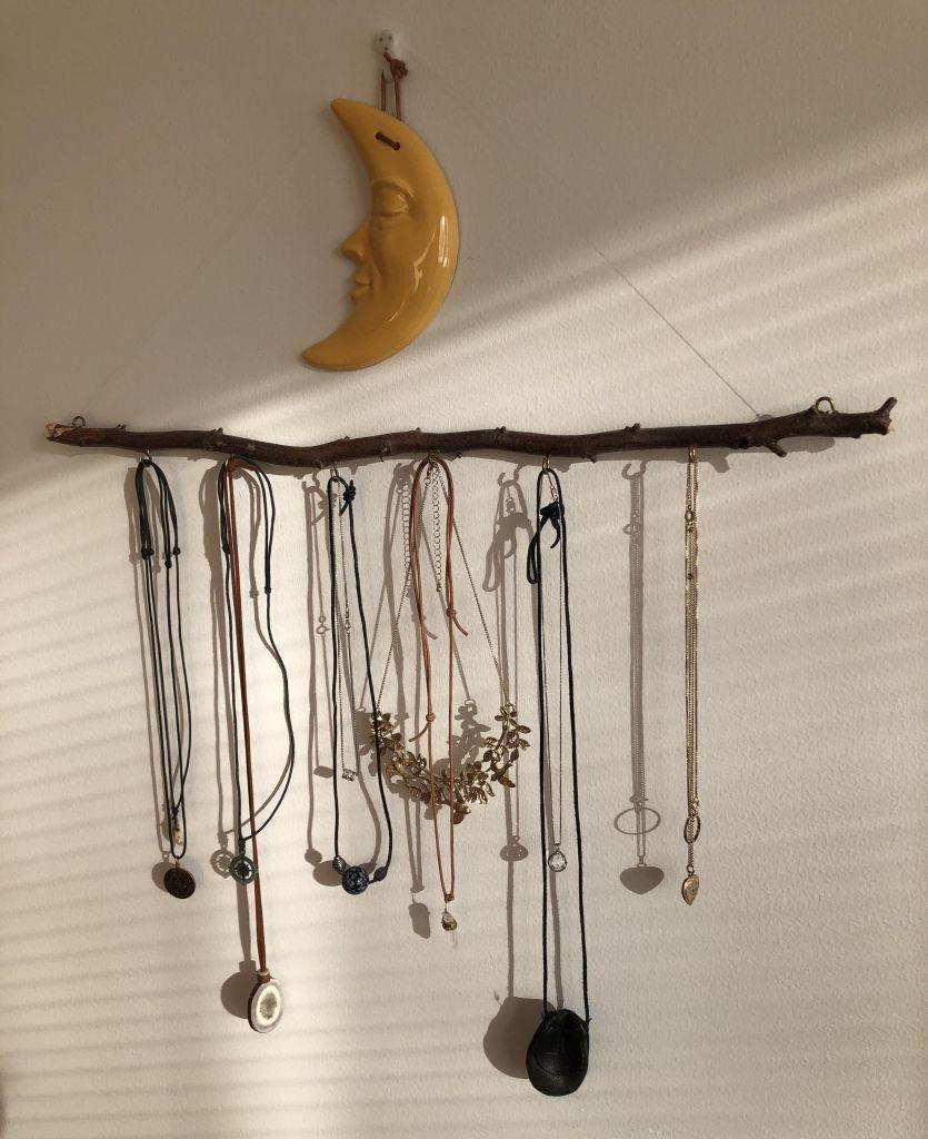 Ast, an dem lange Ketten von Haken hängen wirft Schatten an Wand in Abendsonne