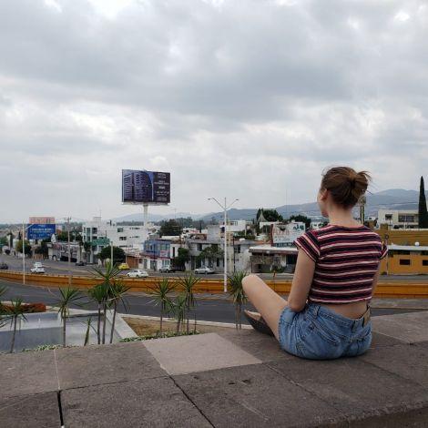 Frau mit dem Rücken zur Kamera sitzt auf einer Plattform über einer Verkehrsstraße