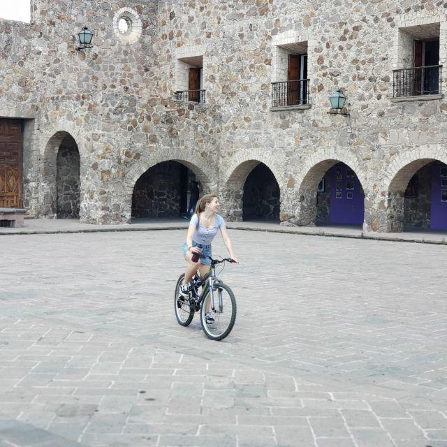 Frau auf Fahrrad mit Monasterium im Hintergrund