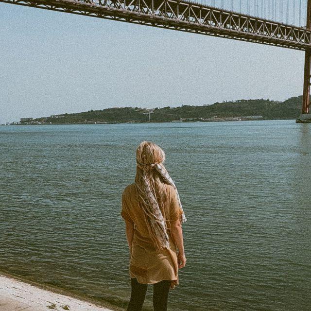 Frau steht an einem Fluss.