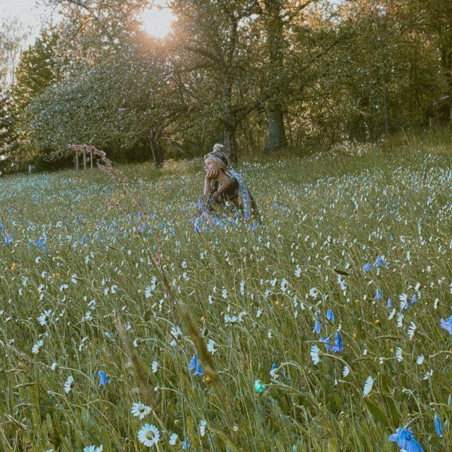 Frau sitzt in bunter Blumenwiese.