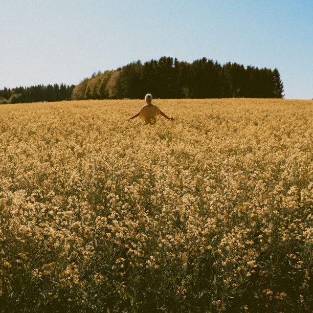 Frau rennt durch Rapsfeld.