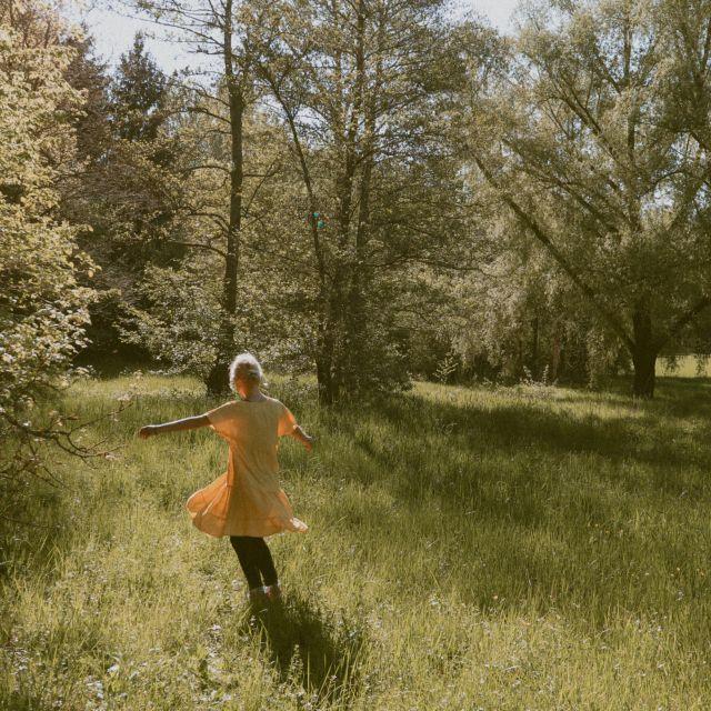 Frau tanzt im Gras in der Natur.