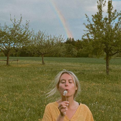 Frau bläst Pusteblume im Vordergrund, Regenbogen im Hintergrund.
