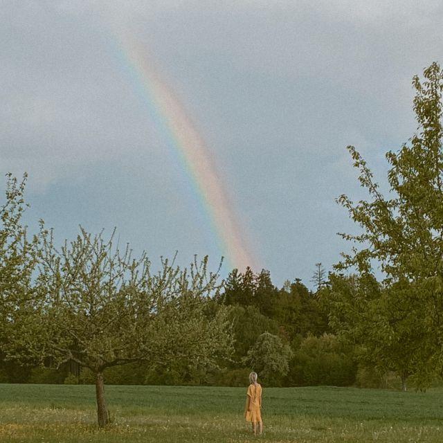 Regenbogen und Frau darunter in der Ferne.