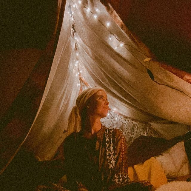 Frau liegt vor einem beleuchteten Indoor-Zelt.
