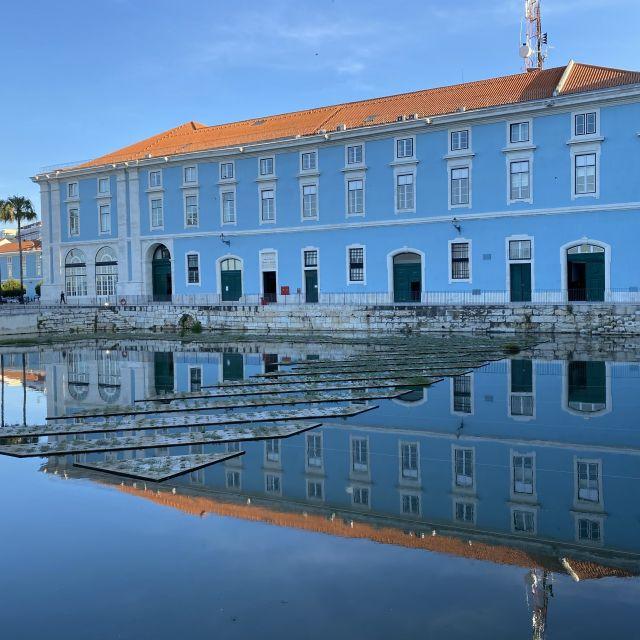 Blaues Gebäude das sich im Wasser spiegelt.