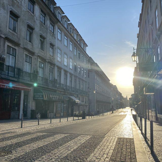 Blick in eine Straße mit Sonne im Hintergrund.