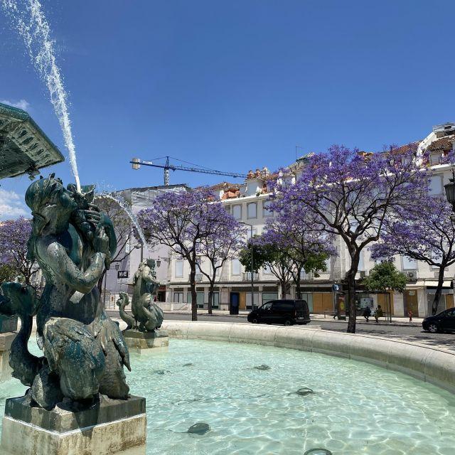 Brunnen und im Hintergrund lila blühende Bäume.