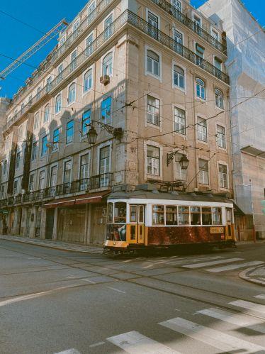 Kleine gelbe Straßenbahn fährt durch die Stadt.