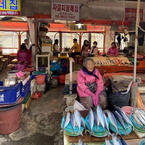 Ältere Frau sitzt an ihrem Stand auf dem Jalgachi Fischmarkt