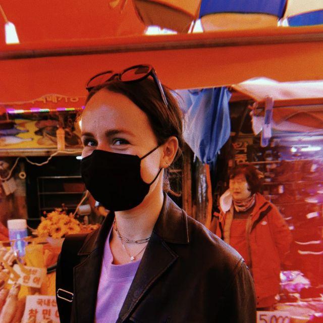 Correspondentin mit Mundschutz lächelt in die Kamera