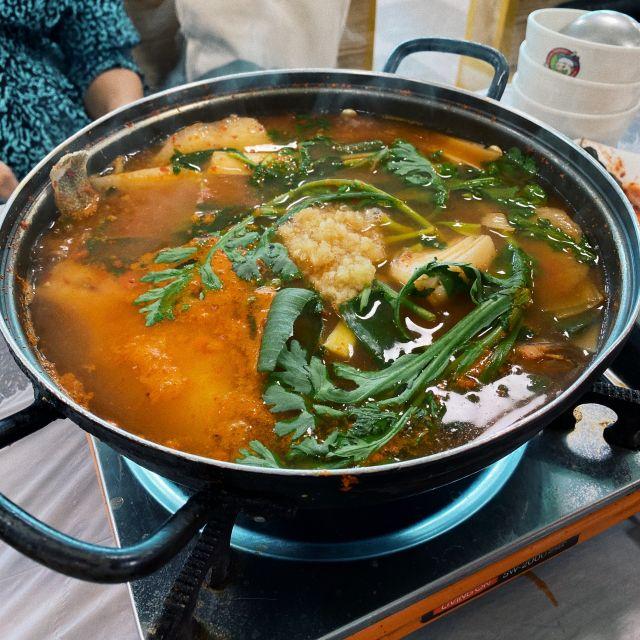 Spicy Fish Stew in einem großen Topf zum Teilen in der Mitte des Tisches