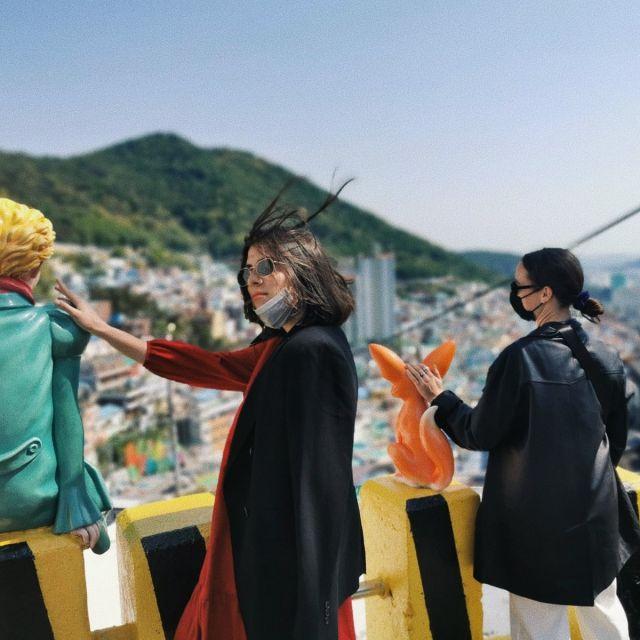 Zwei Frauen mit Comicfigur-Statuen, im Hintergrund ist das Gamcheon Cultural Village zu sehen