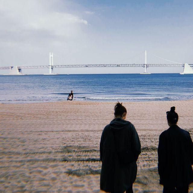 Zwei Frauen von hinten zu sehen beim Strandspaziergang