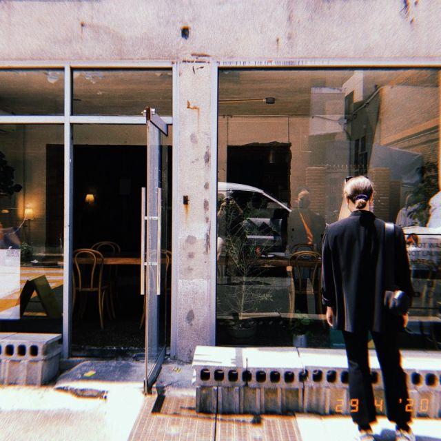 Frau steht vor der Fensterfassade eines Cafés