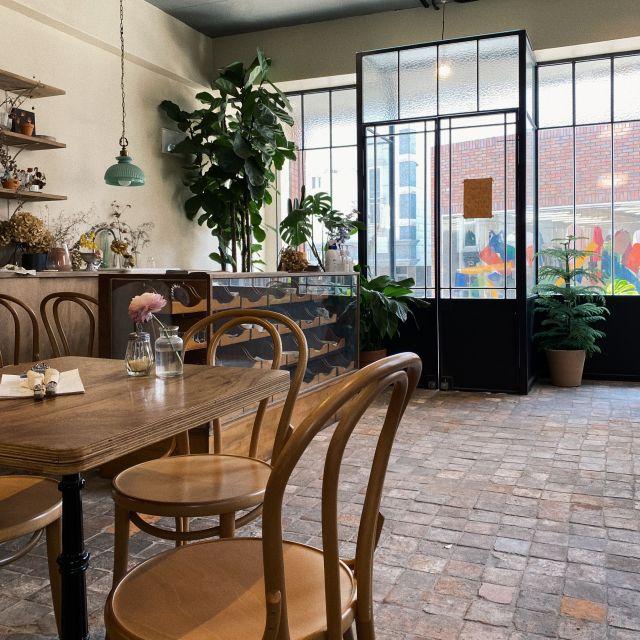 Café von innen mit Bistro-Stühlen und vielen Pflanzen