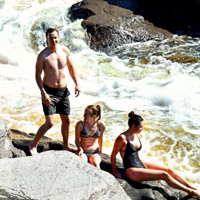 Freunde in Badekleidung an einem Flussufer in Kanada