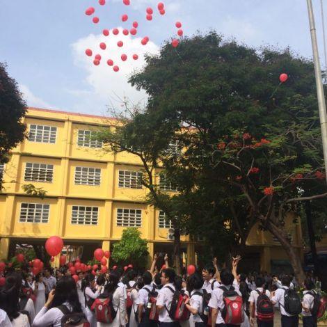 Schülerinnen und Schüler lassen Ballons steigen.
