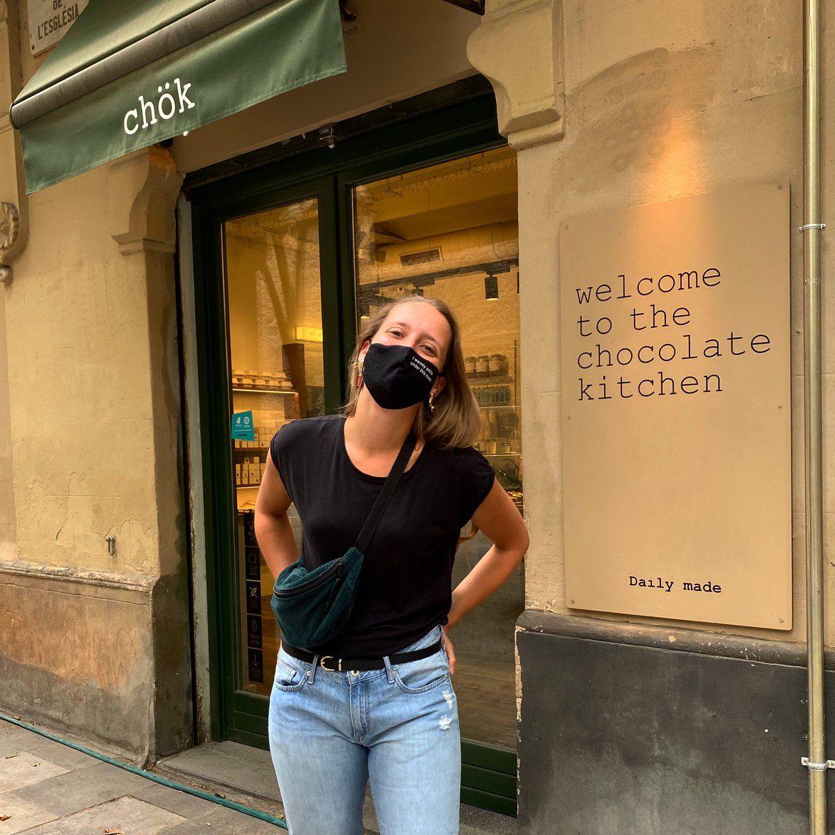 Ein Mädchen, das kit Maske vor einem Restaurant steht.