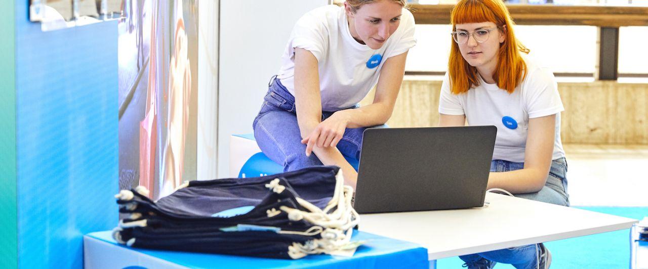Zwei Studentinnen schauen bei einer Messe gemeinsam auf ein Laptop.