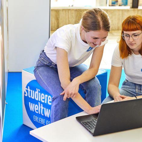 Zwei Studentinnen schauen gemeinsam auf einen Laptop.