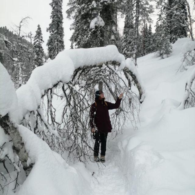 Frau unter gebogenem Ast, verschneite Landschaft
