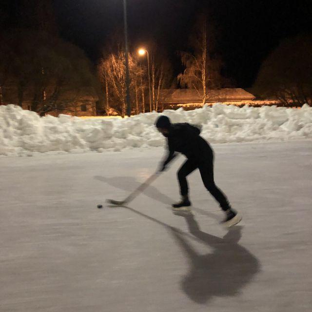 Schlittschufläufer mit Eishockeyschläger und Puk