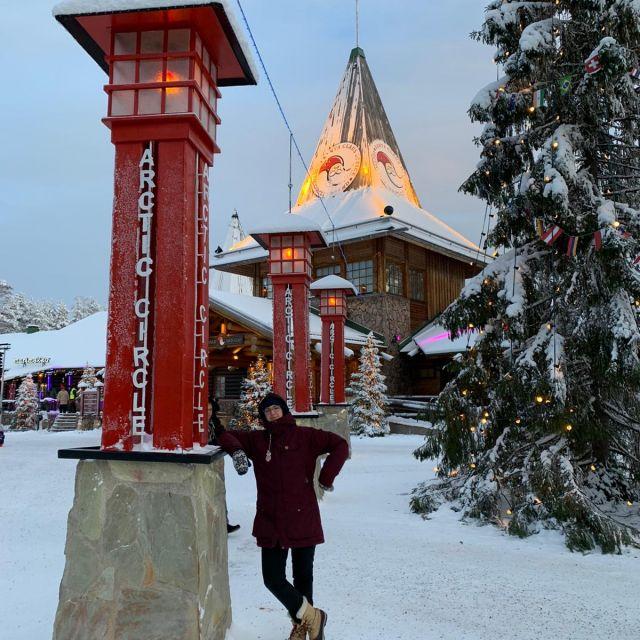 Frau neben roter Säule aufschrift Arctic circle, Schnee und Weihnachtsbaum