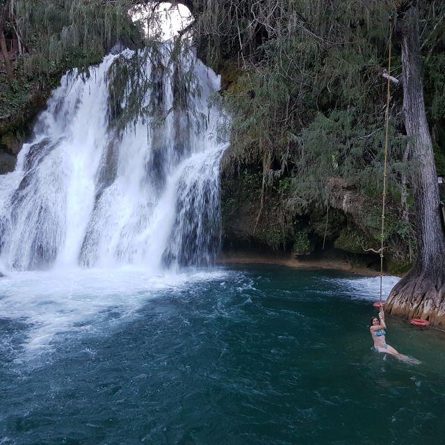 Frau im Wasser mit Wasserfall im Hintergrund