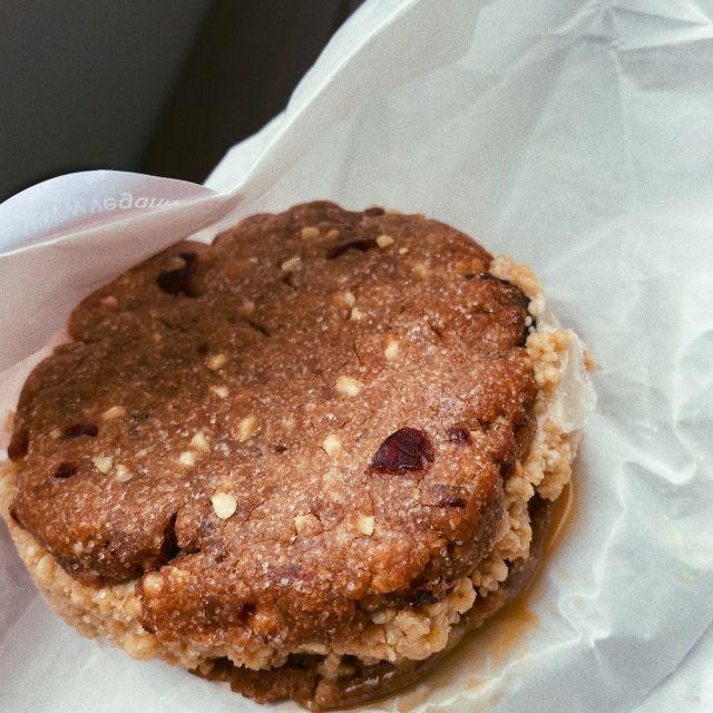 Eine Kugel Erdnussbuttereis mit einem Kern aus Karamellsauce zwischen zwei Erdnussbutterkeksen mit Chocolate Chips und Cranberries, gerollt in gesalzenen Erdnüssen.