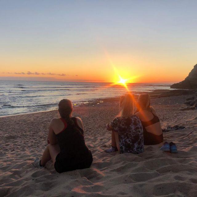Drei Freundinnen beim Sonnenuntergang am Strand.