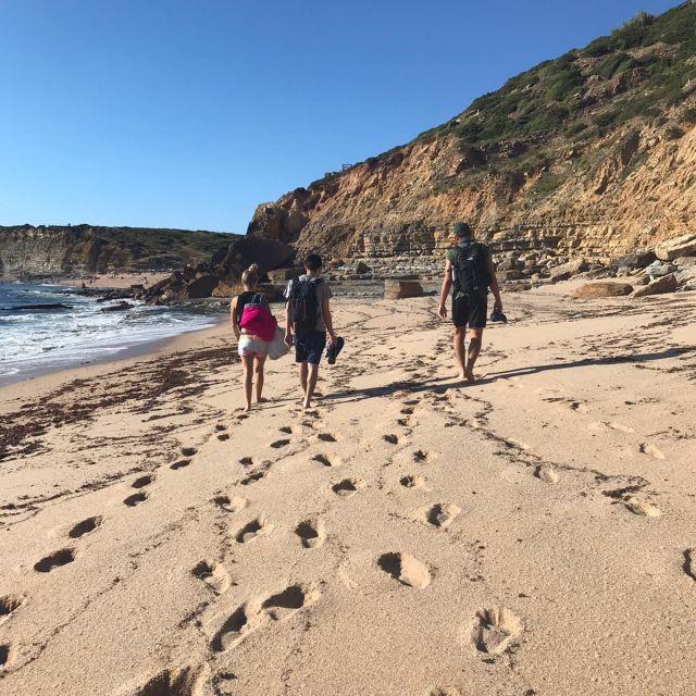 Drei Menschen von hinten am einem verlassenen Strand.